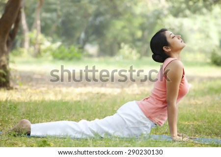 Woman doing yoga in lawn - stock photo