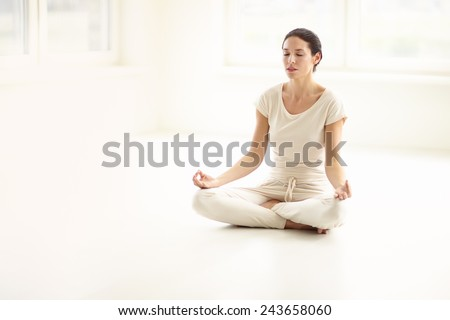 Woman doing yoga in sunny room. - stock photo