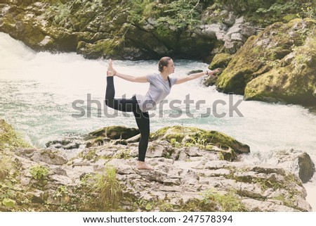 Woman doing yoga in the mountain near the river - stock photo