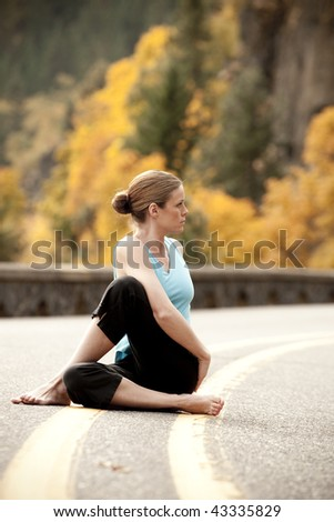Woman doing yoga in the road
