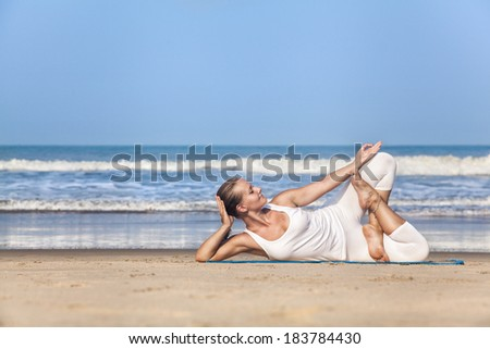 Woman doing yoga in white costume on the beach near the ocean in Goa, India - stock photo