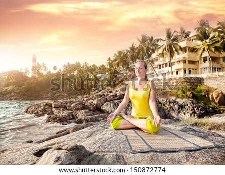 Woman doing yoga meditation in yellow costume on the stone nearby ocean and tropical resort in Kovalam, Kerala, India - stock photo