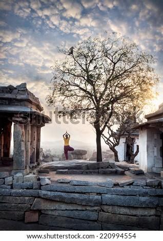 Woman doing yoga near ancient ruins on Hemakuta hill in Hampi, Karnataka, India - stock photo