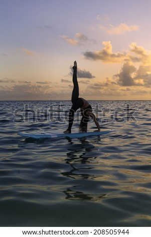 woman doing yoga on a stand-up paddle board in the ocean at sunrise - stock photo