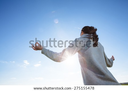woman doing yoga on green grass - stock photo