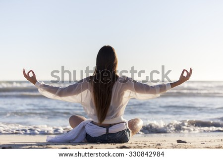 woman doing yoga on the beach  - stock photo