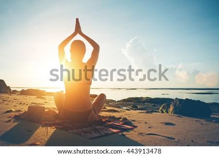 Woman doing yoga on the beach at sunrise - stock photo