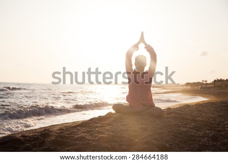 Woman doing yoga on the beach at the sunset