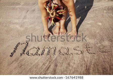 Woman doing yoga on the beach near Namaste handwriting in Goa, India - stock photo
