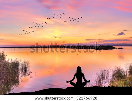 woman doing yoga on the lake - stock photo