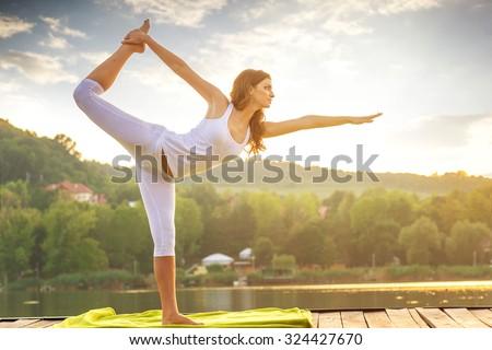 Woman doing yoga on the lake - beautiful lights - stock photo