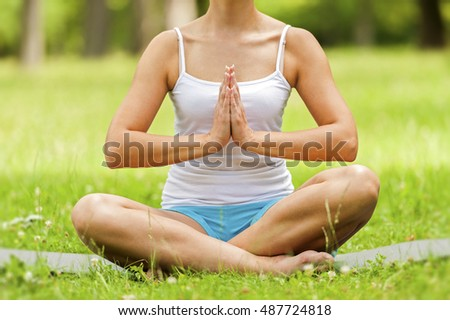 Woman doing yoga on the meadow.