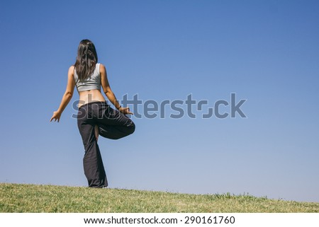Woman doing yoga outdoors - stock photo