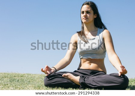 Woman doing yoga outdoors - stock photo