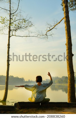woman doing yoga outside in natural environment - stock photo