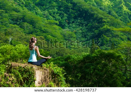 Woman doing yoga over looking a green mountain backdrop.