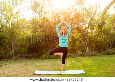 Woman doing yoga poses outside in a park - stock photo