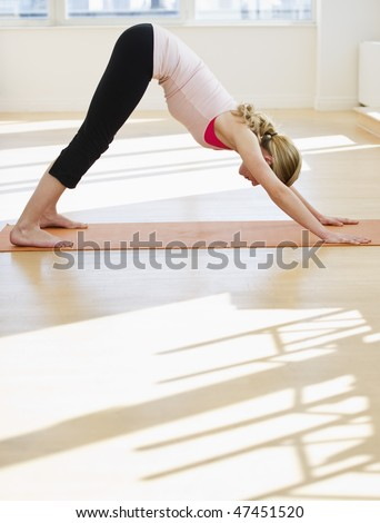 woman doing yoga stretch alone on mat in studio - stock photo