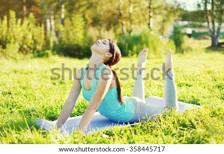 Woman doing yoga stretching exercises on grass in sunny summer day