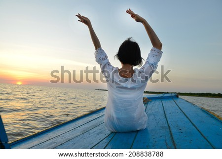 woman doing yoga traveling by wood boat at sunset - stock photo