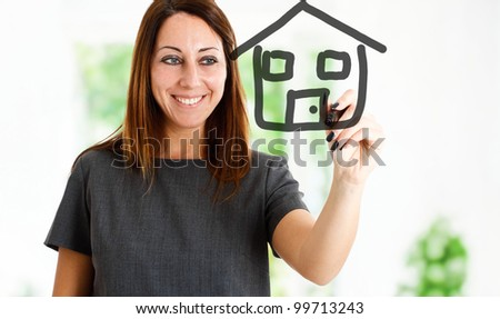 Woman drawing an house on the screen