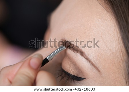 Woman drawing eyebrows on a client with a brush.