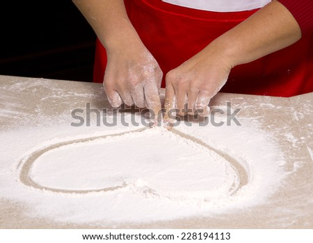 woman drawing into flour heart shape