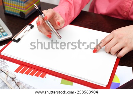 woman drawing on blank clipboard sitting in office - stock photo