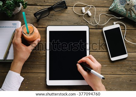 Woman drawing on tablet with pen stylus. Entrepreneur using touchpad on wooden desk with smartphone and detox smoothie drink. - stock photo