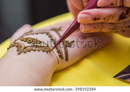 woman draws mehendi on the hands in a beauty salon