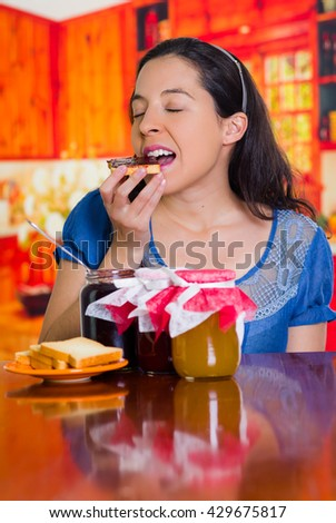 Woman dreaming on her taste of toast and jam, different flavors on the table