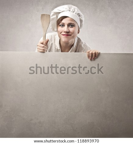 Woman, dressed as a cook, showing her wooden spoon - stock photo