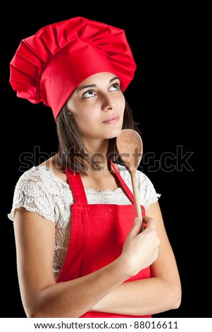 Woman dressed as a cook with cap over black backgound - stock photo