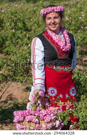 Woman dressed in a Bulgarian traditional folklore costume picking roses in a garden, as part of the summer regional ritual in Rose valley, Bulgaria.