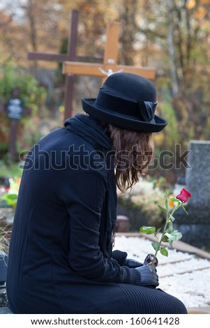 Woman dressed in black sitting at cemetery and holding red rose - stock photo
