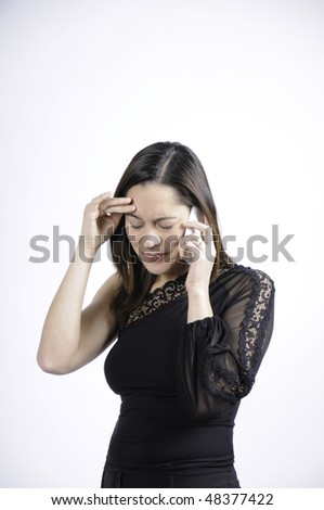 Woman dressed in black talking on the telephone and seems very sad and holding her head. She is of mixed ethnicity. - stock photo