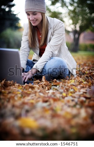 Woman dressed in fall clothing types on her laptop as she sits in the fallen leaves - stock photo