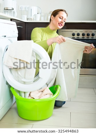Woman dressed in green sweater is washing her towels in a washing machine