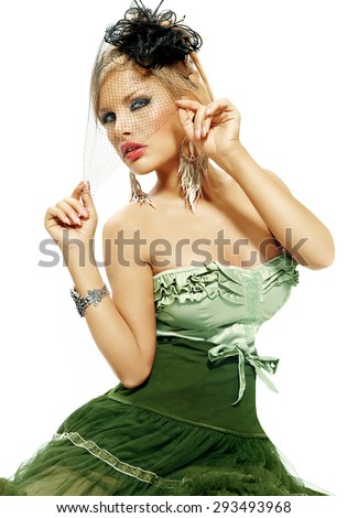 Woman dressed in green velvet dress and small retro hat with veil. Retro style fashion over white background.