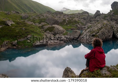 Woman dressed in red is sitting near beautiful blue mountain lake (Georgia, Caucasus Mountains). The woman beholds the mountain landscape. - stock photo