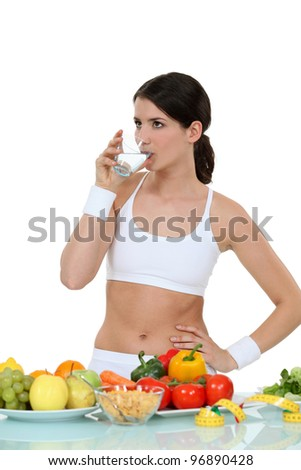 Woman dressed in sportswear stood by vegetables - stock photo