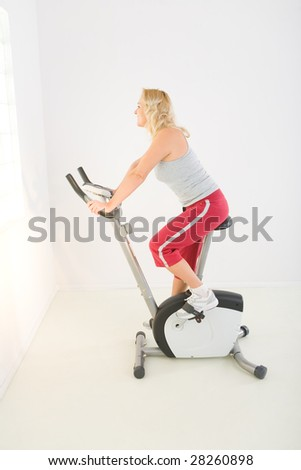 Woman dressed sportswear exercising on bike. She's smiling and looking at camera. - stock photo