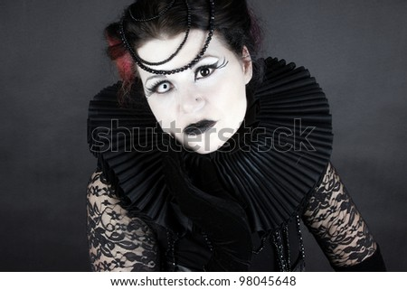 Woman dressed up in gothic style as dark queen in ancient victorian clothing