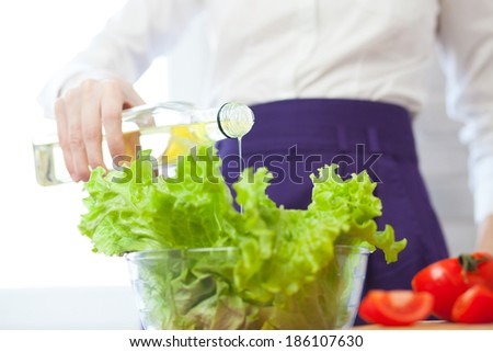 Woman dressing a salad with olive oil - stock photo