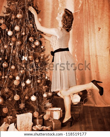 Woman dressing Christmas tree. Black and white.