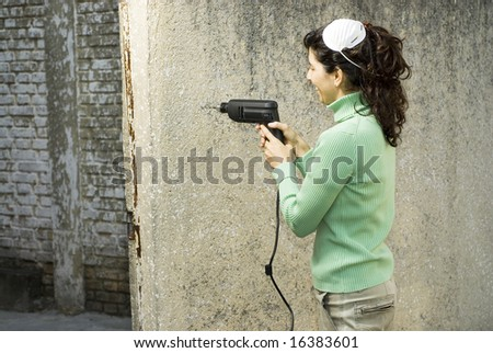Woman drills hole in wall. She is wearing a dust mask on her head. Horizontally framed photo. - stock photo
