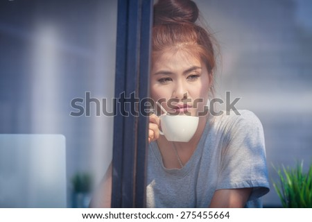 Woman drink coffee in cafe looking pass mirror inattentive absent-minded she thinking sitting at cafe coffee in the morning,adult woman give a toast coffee looking through window - stock photo