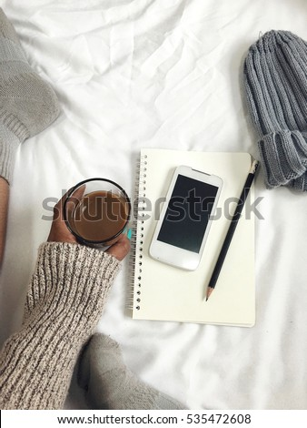Woman drink coffee with smart phone on bed