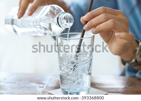 woman drink water with ice in glass on a table in restaurant background - stock photo