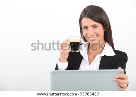 Woman drinking a coffee at her laptop - stock photo